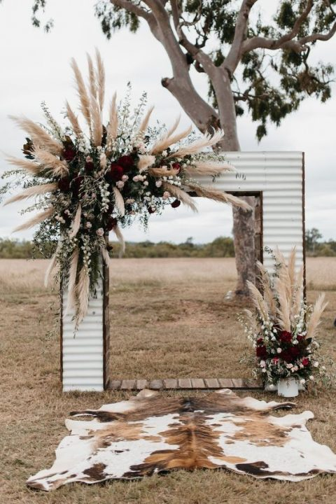 a large wedding arch with dark roses, greenery and pampas grass for a fall boho wedding