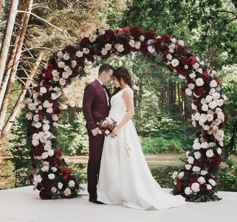 a lush circle wedding arch covered with blush and deep red roses and greenery