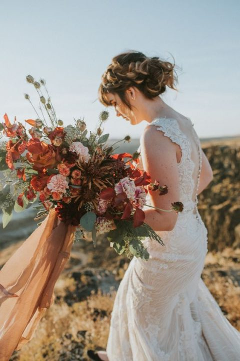 a lush fall-inspired bouquet with rust, red, pink blooms and textural greenery