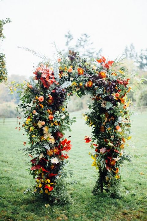 a lush fall wedding arch all covered with greenery, bright orange and yellow blooms