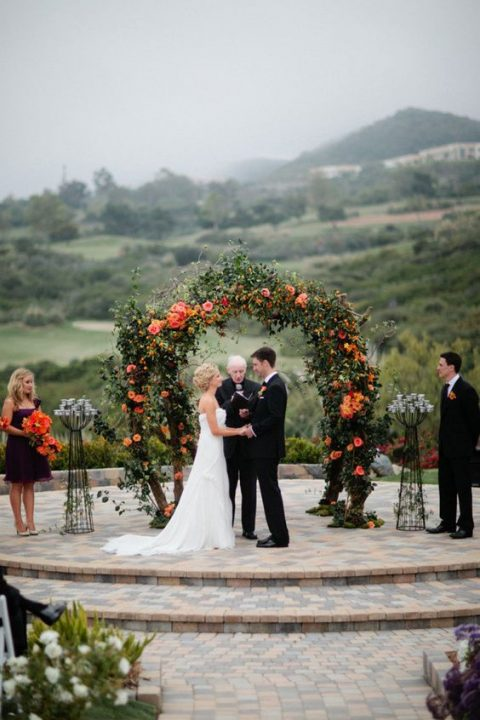 a lush fall wedding arch decorated with a lot of greenery and bold orange blooms