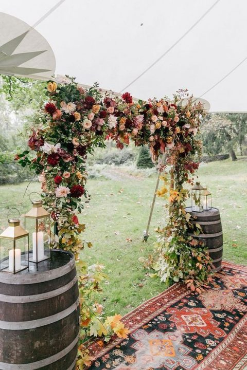 a lush fall wedding arch with blush, burgundy and orange blooms plus fall leaves