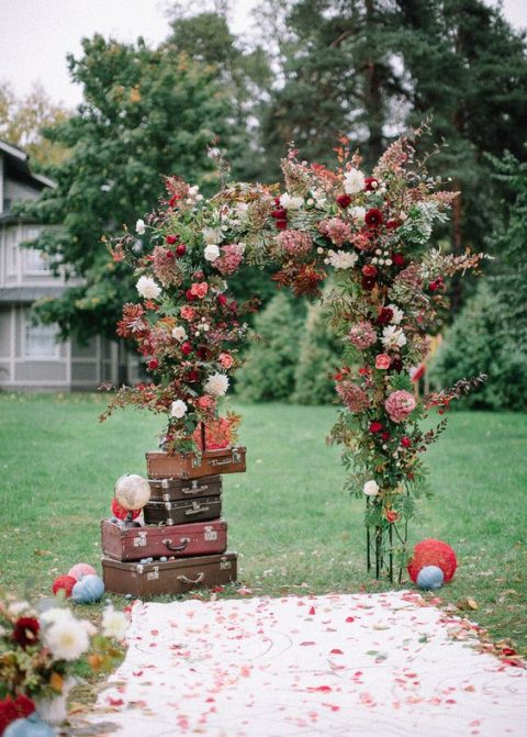 a lush fall wedding arch with greenery and blooms and vintage suitcases for a travel-themed hint