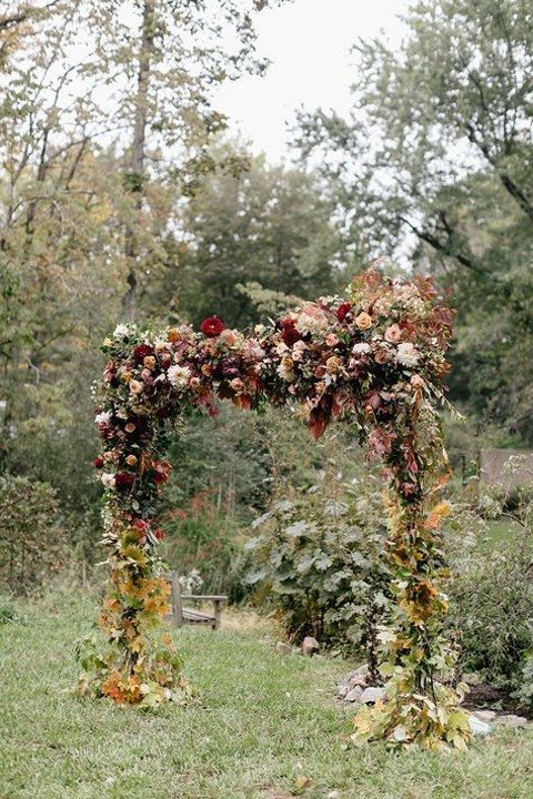 a lush fall woodland wedding arch with blooms and fall leaves