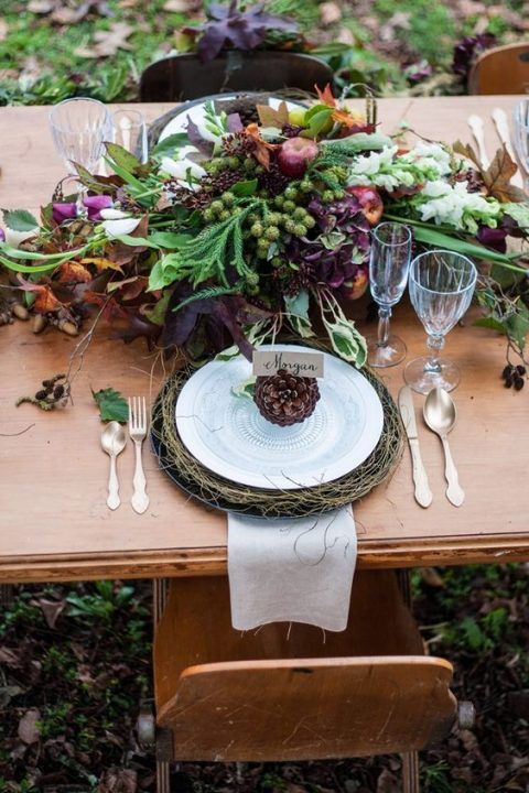 a lush fall woodland wedding table setting with jewel-tone blooms and herbs and pinecones