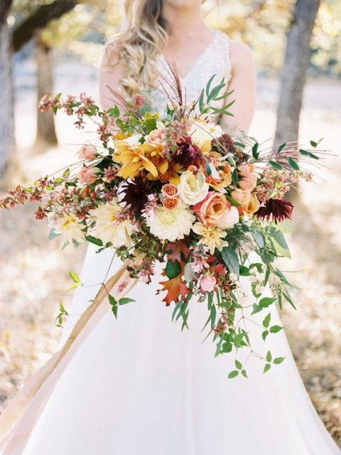 a luxurious and bold fall wedding bouquet with fall leaves, yellow and orange blooms and cascading greenery