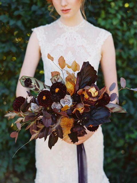 a luxurious moody wedding bouquet with orange and deep purple touches and dark ribbons