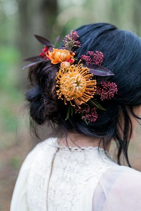a messy bridal hair updo with bold fall blooms and purple foliage