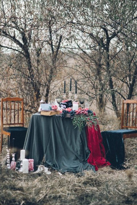 a moody tablescape in black abd red with colored glasses and black candles