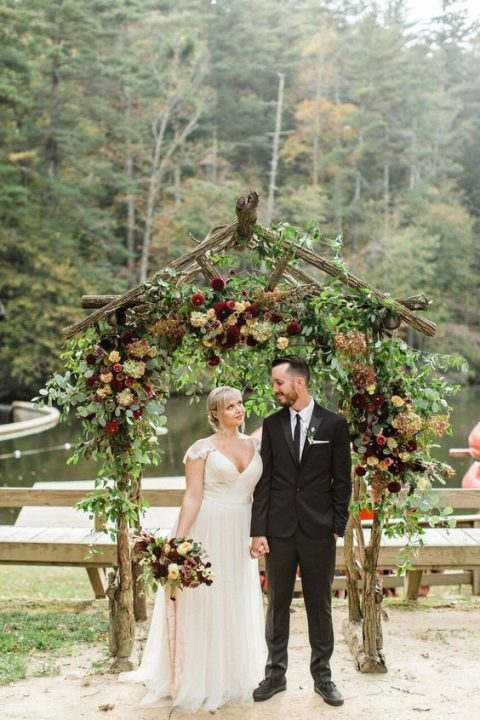 a moody wedding arch with lush greenery and dark blooms