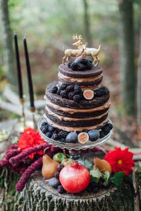 a naked chocolate wedding cake topped with figs and blackberries
