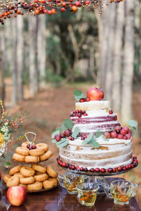 a naked fall wedding cake with apples, grapes and cranberries