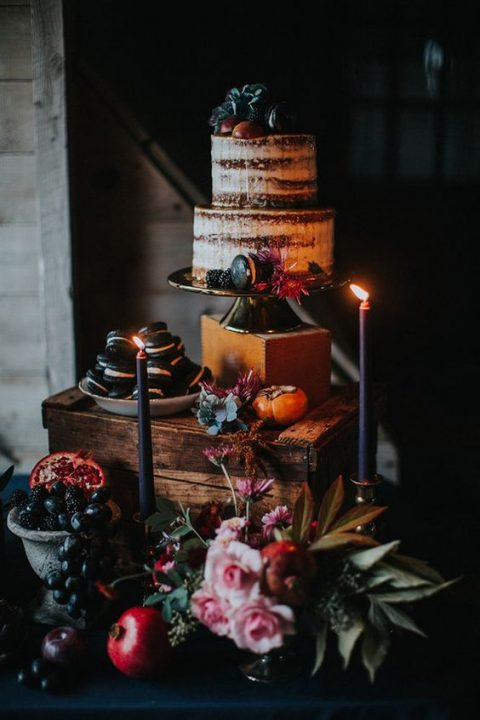 a naked wedding cake topped with blackberries and black macarons