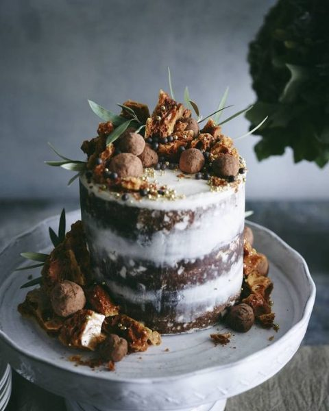 a naked wedding cake with chocolate and pumpkins