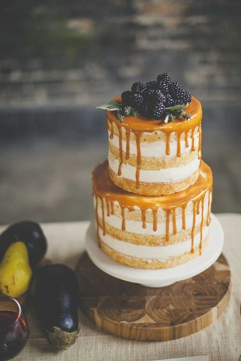 a naked wedding cake with honey drip and blackberries on top