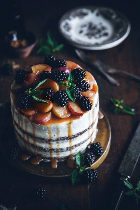 a peach carrot cake with cream cheese frosting, blackberries, peaches and peach drip