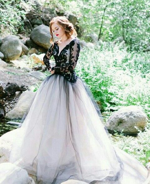 a princess-style wedding gown with a black lace bodice with long sleeves and a skirt with a black overskirt