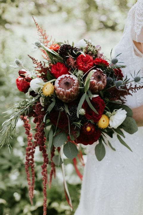 a red protea wedding bouquet with berries, thistles and cascading blooms