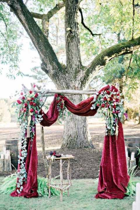 a refined wedding arch with burgundy velvet, eucalyptus and burgundy roses