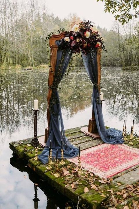a refined wedding arch with dark grey fabric, greenery and dark blooms and foliage