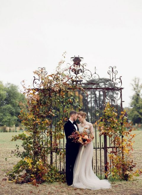 a refined wedding backdrop of a vintage gate and fall leaves and greenery