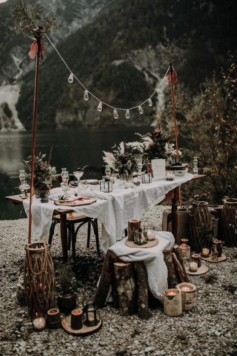 a rustic boho reception space by the lake with candles, bulbs and textural greenery decor