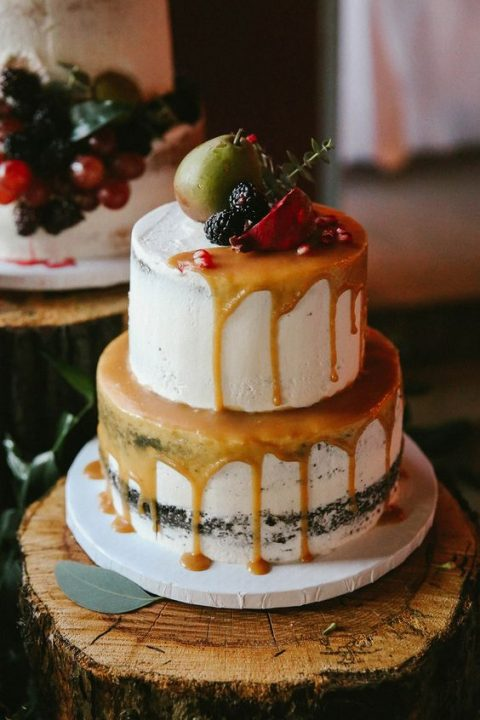 a semi naked cake with caramel drip, topped with a pear, blackberries and a pomegranate