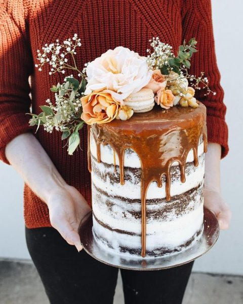 a semi naked chocolate cake with salted caramel drip, fresh blooms and macarons