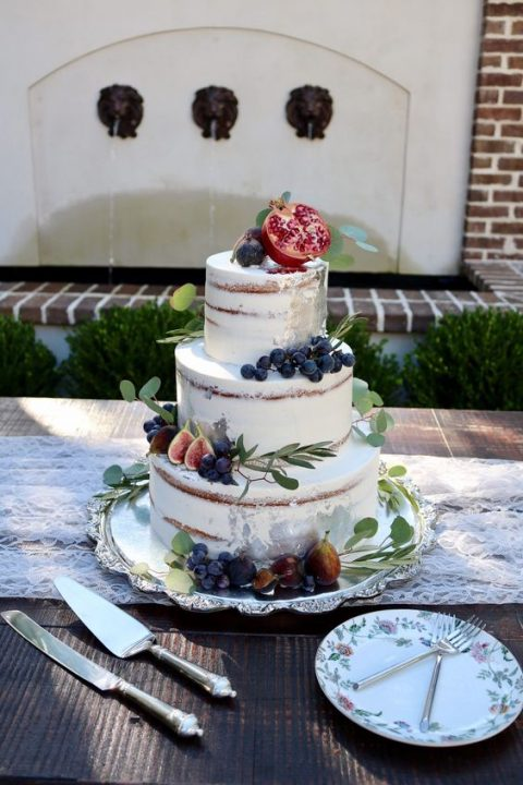 a semi naked wedding cake topped with fersh greenery and fruits