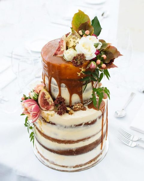 a semi naked wedding cake with caramel drip and blooms and foliage on the top