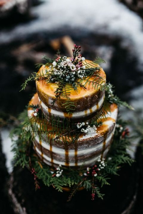 a semi naked wedding cake with caramel drip and some greenery