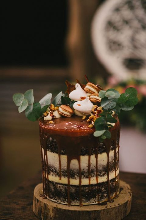 a semi naked wedding cake with caramel drip, topped with eucalyptus, macarons and meringues