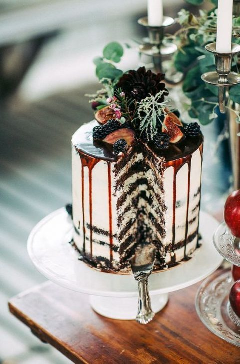 a semi-naked wedding cake with chocolate drip, figs, blackerries and blooms on top