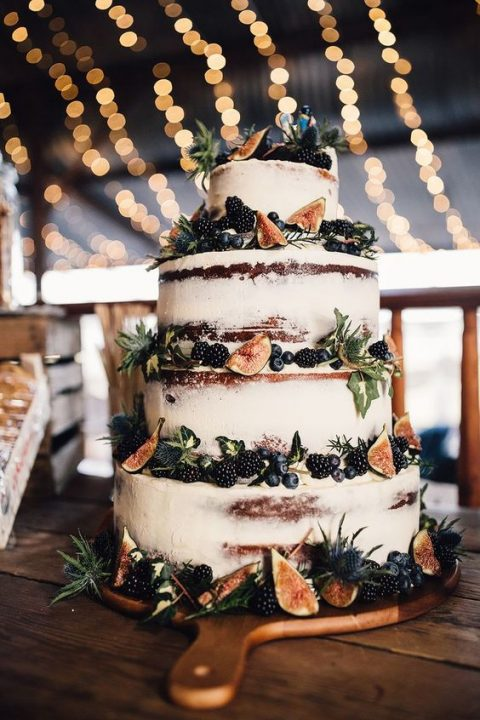 a semi naked wedding cake with figs and berries