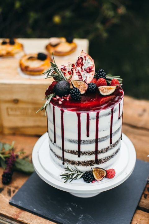 a semi naked wedding cake with pomegranate drip topped with fruits