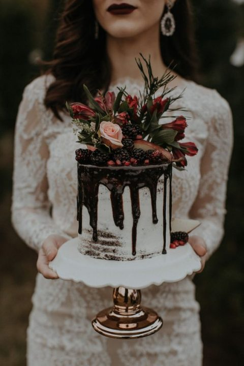 a semi naked wedidng cake topped with berries and bold blooms plus chocolate drip