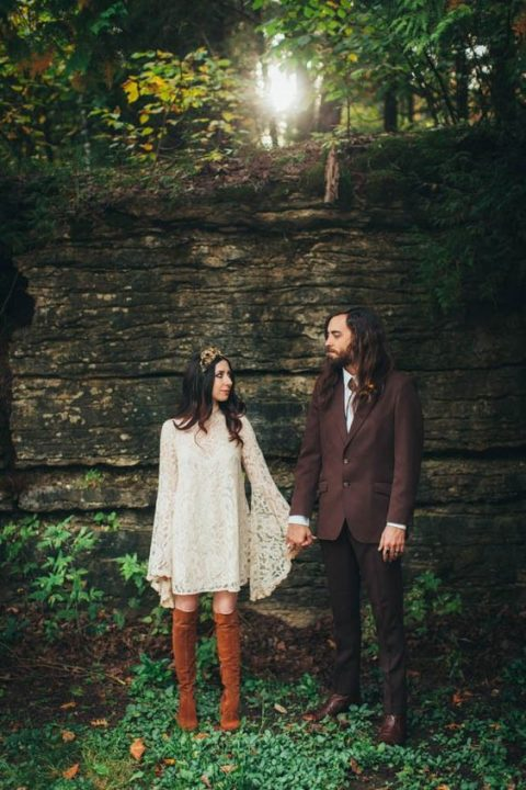 a short ivory lace wedding dress with bell sleeves and rust-colored suede boots