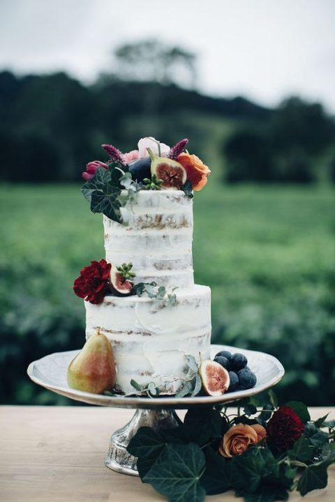 a simple semi naked wedding cake with fruits and foliage on top