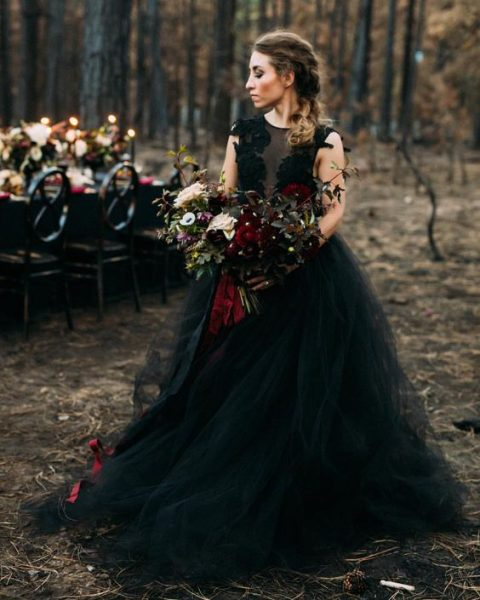 a sleeveless princess-styled black wedding gown with a lace bodice and an illusion neckline plus a tulle skirt