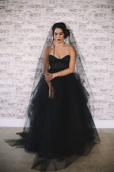 a strapless princess-style black wedding gown with a layered skirt and a long black veil