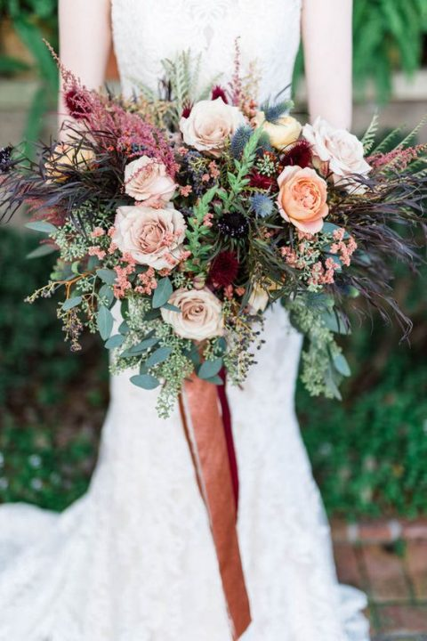 a super textural wedding bouquet with peachy and burgundy blooms, greenery and grasses