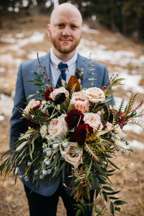 a textural and cascading wedding bouquet with blush and burgundy blooms plus grasses and greenery