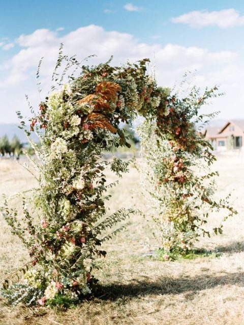 a textural fall wedding arch adorned with lush greenery, pampas grass and neutral blooms