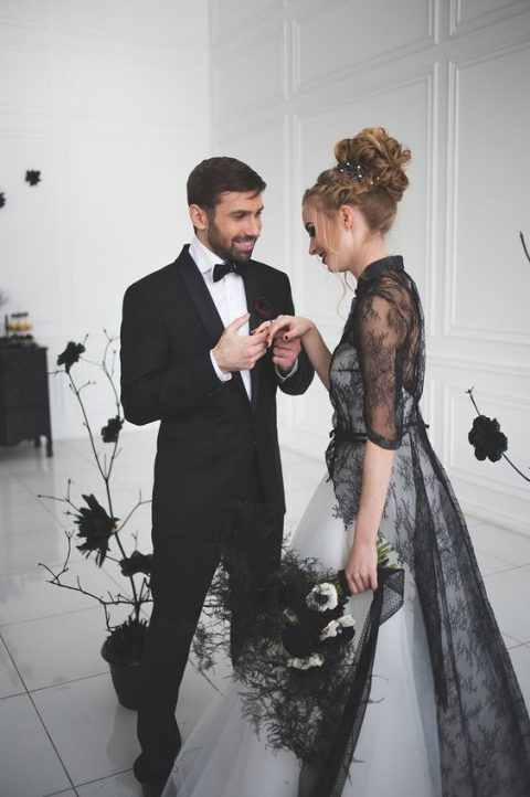 a white strapless A-line wedding dress with a black lace overdress with long sleeves and a train