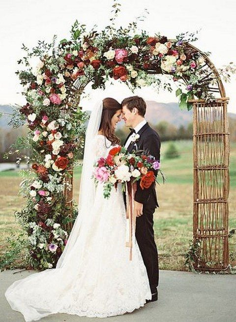 a wicker wedding arch adorned with burgundy, dark purple, white and pink bloos and greenery