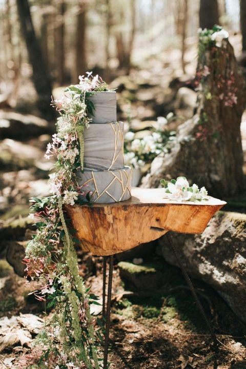 a woodland cake display with a tree stump table and cascading greenery