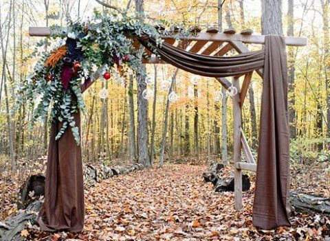 a woodland fall wedding arch with brown fabric, eucalyptus, candles in glass bubbles and apples