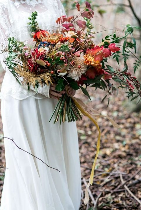 a woodland wedding bouquet with berries, dahlias, ferns and leaves