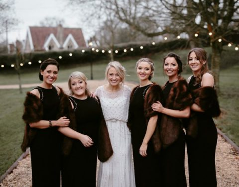 elegant black halter neckline bridesmaid gowns with embellished sleeves and faux fur coverups