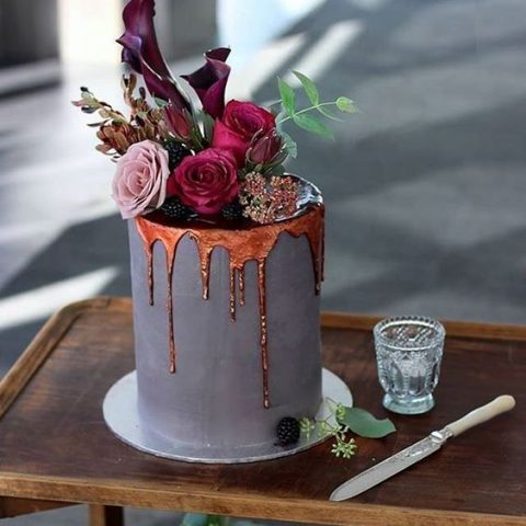 matte grey wedding cake with molten copper drip topped with blackberries and flowers